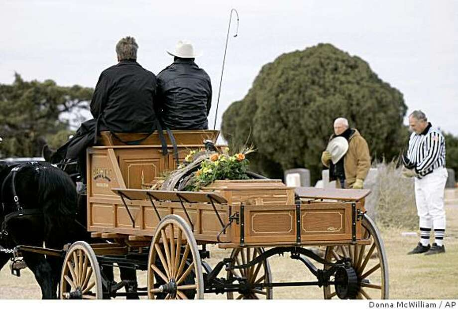 A horse-drawn wagon carries the saddle-draped casket of  Hall of Fame quarterback Sammy Baugh to his burial site near Rotan, Texas, Monday, Dec. 22, 2008. Ted Posey, left, and his son Jeff Posey, stand in remembrance of Baugh for both his ranching and football careers. (AP Photo/Donna McWilliam) Photo: Donna McWilliam, AP