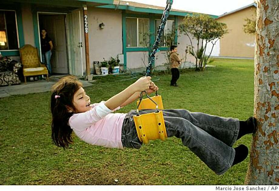Fatima Rivas, 6, swings in front of a house shared by two families in Mendota, Calif., Wednesday, Dec. 10, 2008. Rivas' parents, both farmworkers,  have been out of work since October.  A double whammy of drought and a court-ordered cutback of water supplies has cost California's agricultural heartland Millions of dollars in lost planting, affecting workers in the nation's produce capital. (AP Photo/Marcio Jose Sanchez) Photo: Marcio Jose Sanchez, AP