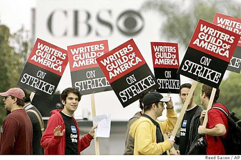 Picketers march outside the entrance to CBS Television City in Los Angeles as a strike by film and television writers got under way Monday, Nov. 5, 2007. The contract between the 12,000-member Writers Guild of America and the Alliance of Motion Picture and Television Producer expired Oct. 31. Talks that began this summer failed to produce much progress on the writers' key demands for a bigger slice of DVD profits and revenue from the distribution of films and TV shows over the Internet. Photo: Reed Saxon, AP