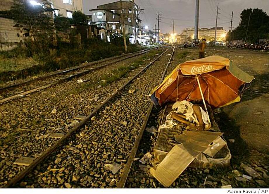 **APN ADVANCE FOR SUNDAY DEC.21**  A Trolley boy sleeps beside the tracks in Sta. Mesa, Manila, Philippines on Friday Nov. 14, 2008. (AP Photo/Aaron Favila) Photo: Aaron Favila, AP