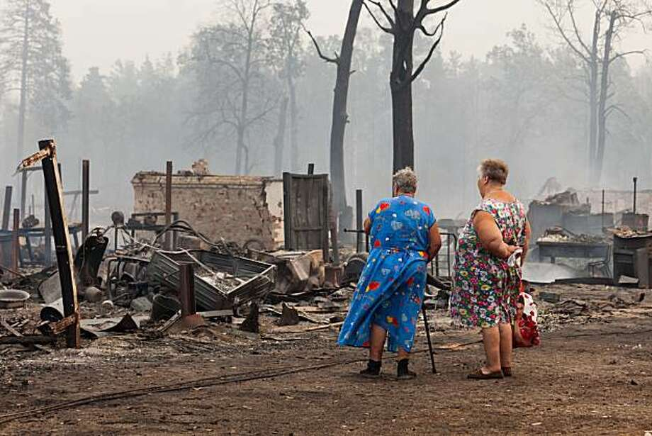 Women, local  residents, look at what is left of buildings burned to the ground in the village of Mokhovoe which was  destroyed by a forest fire near the town of Lukhovitsy some 135 km (84 miles) southeast of Moscow, Friday, July 30, 2010. The fires havespread quickly across more than 200,000 acres (90,000 hectares) in recent days after a record heat wave and severe drought that has plagued Russia for weeks. Photo: Ilya Varlamov, AP