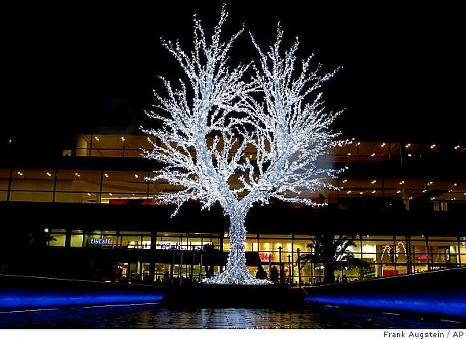 An illuminated tree is seen in front of the Christmas market in Duisburg, western Germany, Friday Dec. 5, 2008. (AP Photo/Frank Augstein) Photo: Frank Augstein, AP