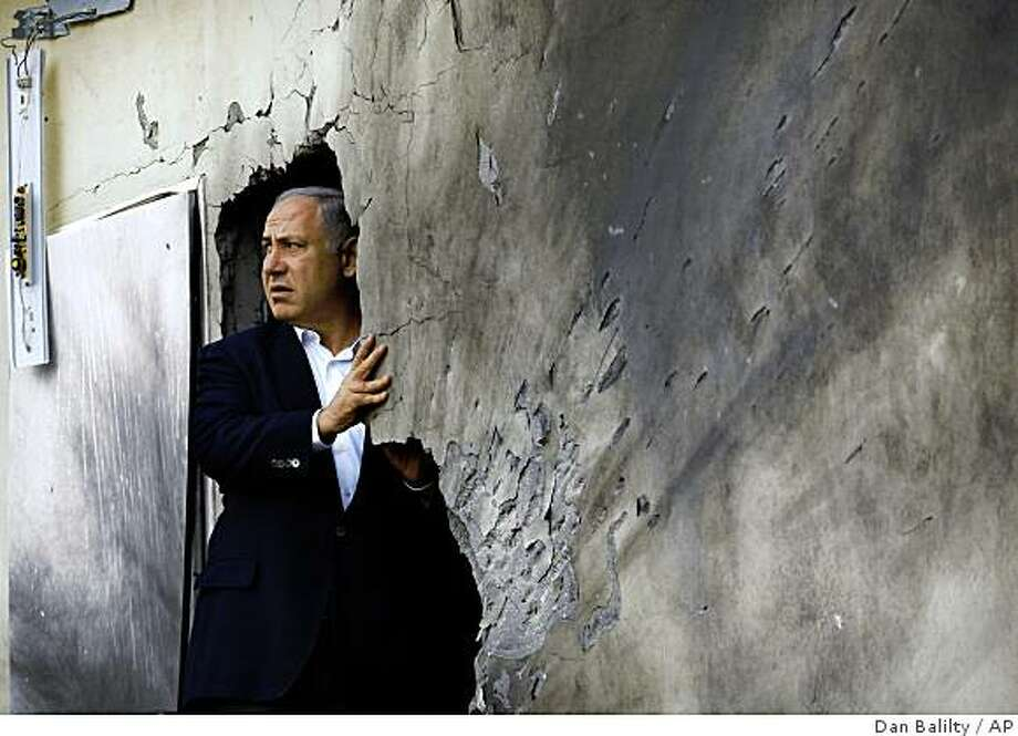 Israeli Likud party leader Benjamin Netanyahu inspects the damage of a house hit by a rocket, fired by Palestinian militants from the Gaza Strip, in the southern town of Sderot Sunday, Dec. 21, 2008. Barrages of rockets fired from Gaza hit Israeli towns Sunday and the Israeli air force responded with a missile strike as violence surged following the official expiry date of a shaky truce. (AP Photo/Dan Balilty) Photo: Dan Balilty, AP