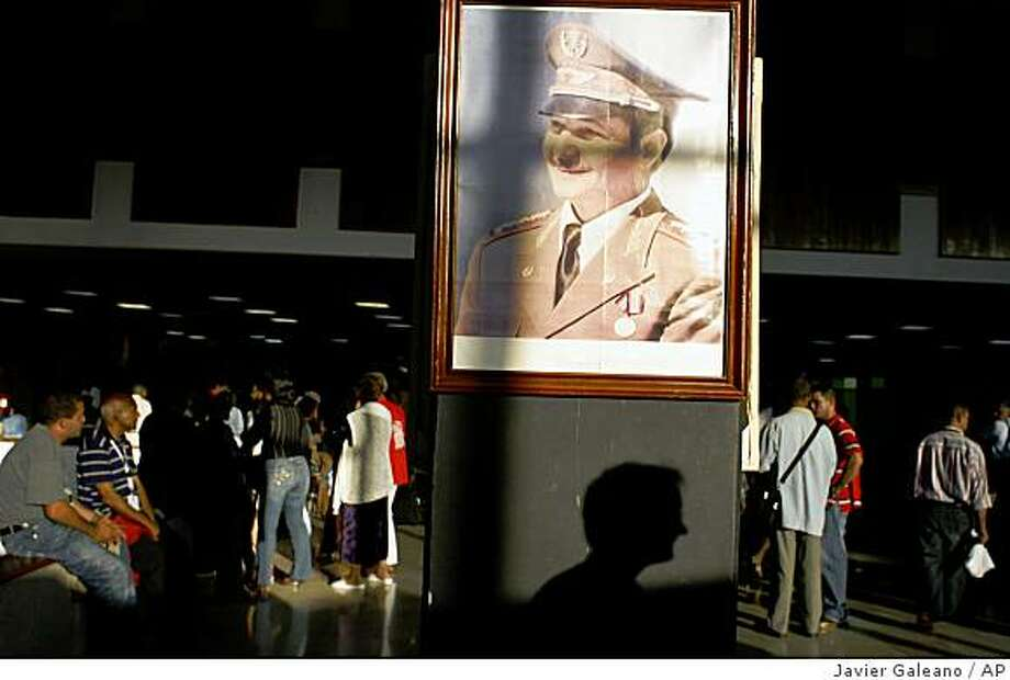 ** ADVANCE FOR SUNDAY, DEC. 21 ** An image of Cuba's President Raul Castro hangs during the 7th Committee for the Defense of the Revolution Congress in Havana, Sunday, Dec. 14, 2008. The Cuban revolution triumphed on Jan. 1, 1959 after dictator Fulgencio Batista fled the country and Fidel Castro and his band of rebels descended from the island's eastern mountains, where they waged a guerrilla war against government troops. Cuba will celebrate on Jan.1, 2009 the 50th anniversary of the triumph of the revolution. (AP Photo/Javier Galeano) ** NO ONLN ** NO IONLN ** Photo: Javier Galeano, AP