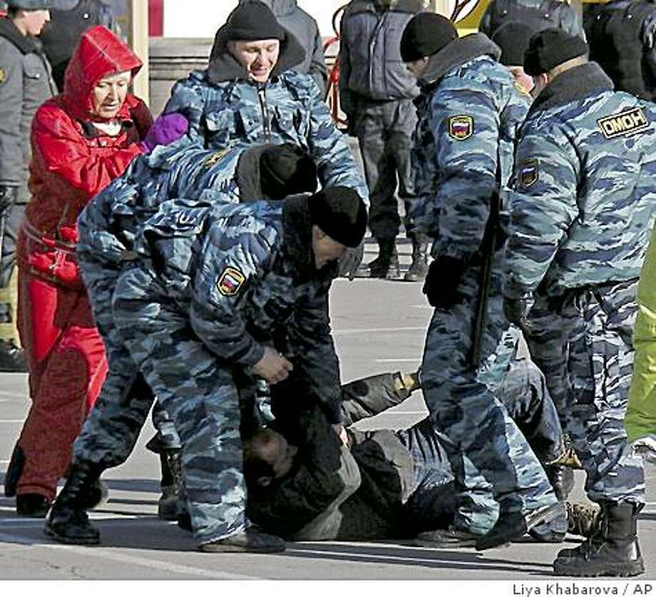 Riot police officers detain a protestor during a demonstration against the authorities' plans to raise tariffs on imported used Japanese cars, in Vladivostok, some 6,400 kilometers (4,000 miles) east of Moscow, Sunday, Dec. 21, 2008. Police beat and detained motorists who tried to rally in Vladivostok to protest the government's decision to raise car import tariffs. (AP Photo/Liya Khabarova) Photo: Liya Khabarova, AP