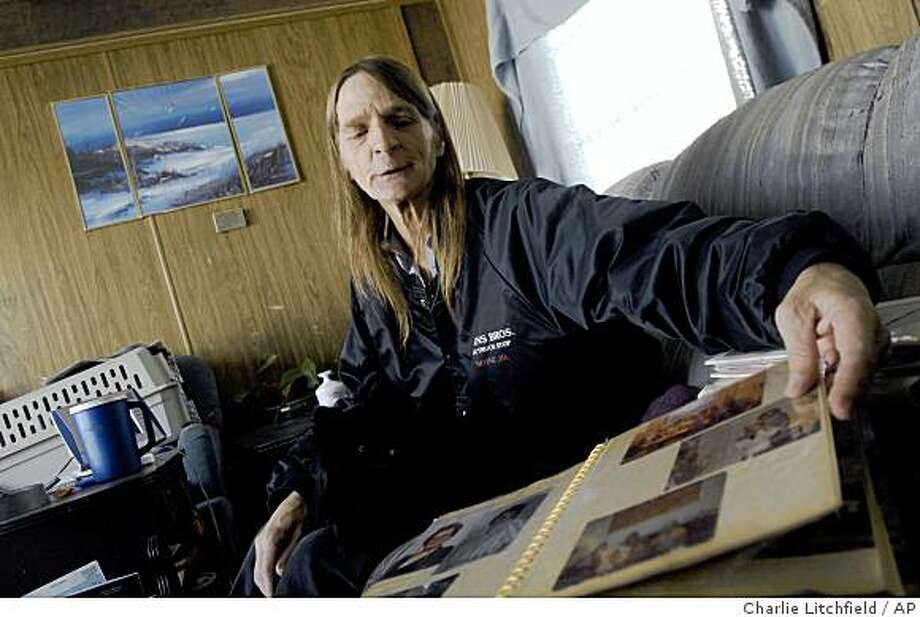 ** FOR RELEASE DEC. 13-14 OR THEREAFTER **Catherine Carlson, 52, of Payette, flips through photo albums Tuesday, Dec. 9, 2008  at her trailer in Payette, Idaho. Carlson, who underwent a gender transformation procedure nearly 30 years ago has been in jail four times in the past year stemming from an initial citation which included both her legal name and the one she was born with.  (AP Photo/Charlie Litchfield) Photo: Charlie Litchfield, AP