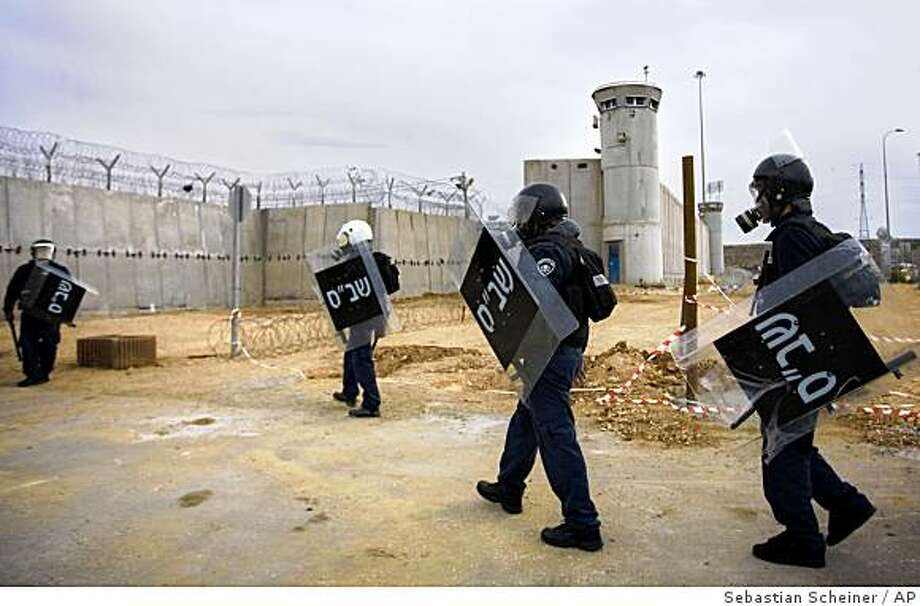 ** CORRECTS DATE ** Israeli prison guards wearing gas masks and riot gear enter Ofer prison during clashes with Palestinian inmates near the West Bank city of Ramallah, Saturday, Dec. 20, 2008. Seven Palestinian inmates and three Israeli prison guards were injured in clashes after authorities had tried to search the tents in which the inmates sleep, Israeli sources said. The prisoners refused, and immediately began to throw objects at the guards, Israeli prison officials said. (AP Photo/Sebastian Scheiner) Photo: Sebastian Scheiner, AP