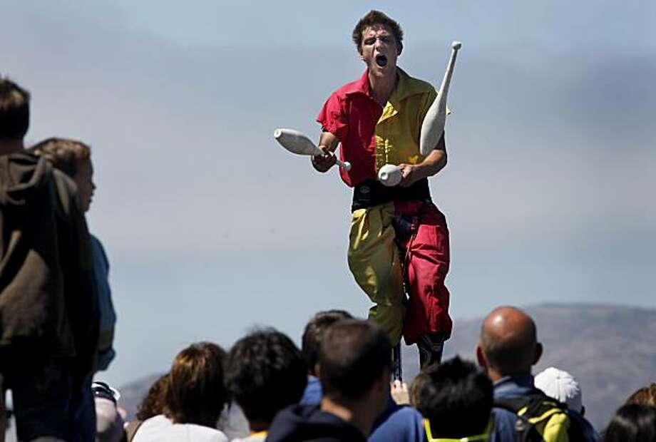 Alex Griffiths of the Sardine Family Circus had one of the largest crowds as he juggled while balancing on a ladder.  The first day of August 2010 in San Francisco, Calif. looked healthy for merchants of every variety at Fisherman' Wharf as the sidewalks were packed with people and the weather was pleasant. Photo: Brant Ward, The Chronicle