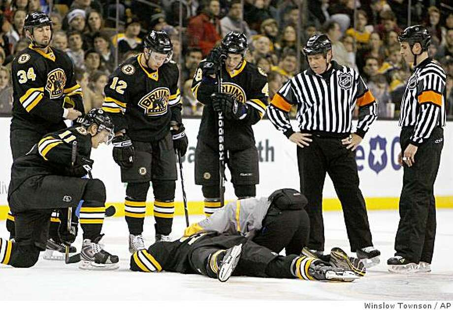 Referees and Boston Bruins' P.J. Axelsson (11), Shane Hnidy (34), Chuck Kobasew (12), and Matt Hunwick stand over fallen Bruin Patrice Bergeron during the second period of their 4-2 win over the Carolina Hurricanes in a game in Boston Saturday, Dec. 20, 2008. Bergeron left the game and did not return. Photo: Winslow Townson, AP