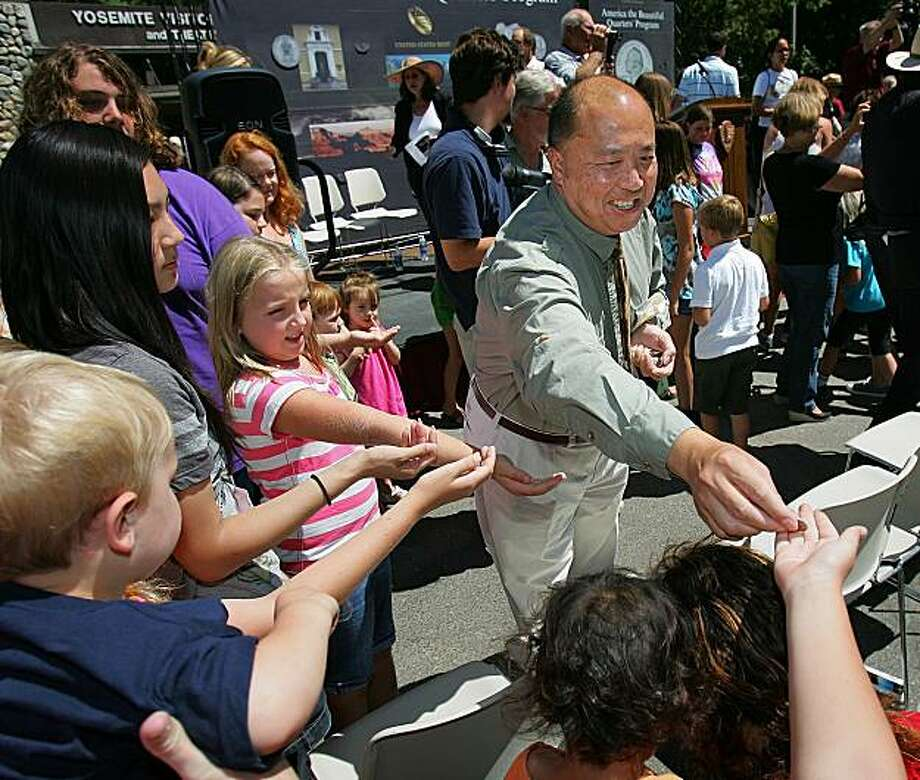 US Mint Director Ed Moy hands out coins to kids after the release of the Yosemite National Park Quarter on Thursday, July 29, 2010 in Yosemite, Calif. Photo: Gary Kazanjian, AP