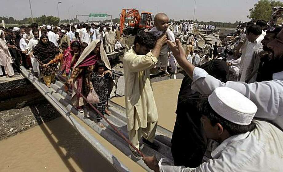 People walk over a makeshift bridge set-up over the damaged portion of a main highway in flood hit area Charsadda, Pakistan on Saturday, July 31, 2010. Flooding in Pakistan has killed more than 800 people in a week, a government official said Saturday asrescuers struggled to reach marooned victims and some evacuees showed signs of fever, diarrhea and other water borne diseases. Photo: Mohammad Sajjad, AP