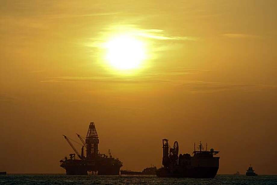 """The Transocean Development Driller III, left, works to drill the primary relief well during sunrise at the BP Plc Macondo well site in the Gulf of Mexico off the coast of Louisiana, U.S., on Friday, July 30, 2010. BP Plc's """"static kill"""" procedure may be delayed by a day because the company first has to remove debris at the bottom of the relief well drilled to permanently plug the source of the largest oil spill in the U.S. history. Photographer: Derick E. Hingle/Bloomberg Photo: Derick E. Hingle, Bloomberg"""