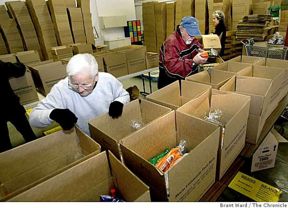 Eva Westcott, left, and Hank Franzini readied some food boxes for a group in Novato. A group of volunteers gathered at the Marin County Community Food bank to pack food holiday boxes Tuesday, December 16, 2008. Season of Sharing supports the Marin food bank. Photo: Brant Ward, The Chronicle