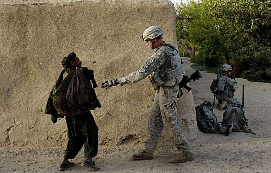 A US soldier of 2nd Platoon Bravo Troop of 1st Squadron, 71st Cavalry frisks an Afghan villager during a patrol in the Dand district of Kandahar Province on July 26, 2010.  Afghanistan's president Karzai has ordered a probe into a rocket attack which his office said killed an unspecified number of people, as leaked documents laid bare the civilian toll of the US-led war. Photo: Manpreet Romana, AFP/Getty Images