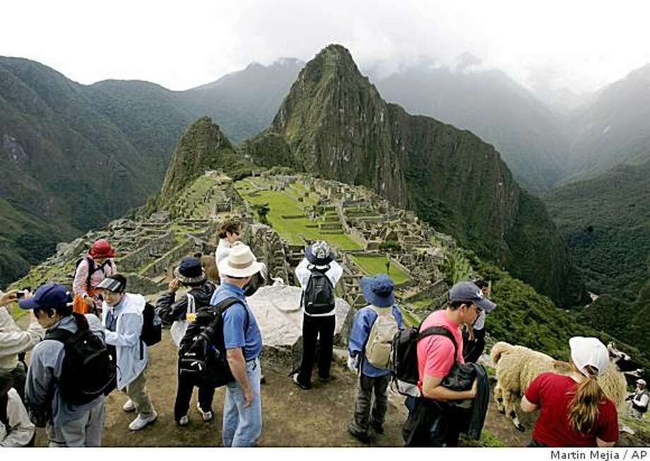 People tour the ruins of Machu Picchu near Cuzco, Peru, Wednesday, March 26, 2008. Peru's tourism industry is booming. Visits to Machu Picchu, Peru's top tourist destination, have more than doubled in the last decade to 800,000 people, along with the price of getting there. Cuzco now has a half dozen four- and five-star hotels. That compares with two in the early 1990's, when the city was a haven for daring travelers defying U.S. State Department warnings against the bloody Shining Path insurgency. Photo: Martin Mejia, AP