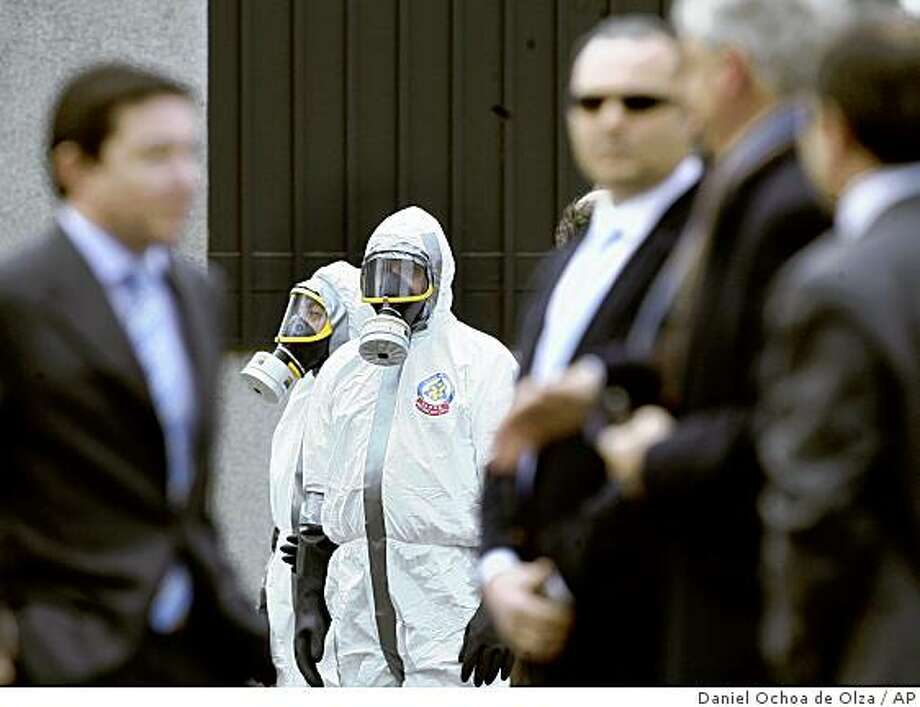 Explosive and chemical experts arrive to check a suspicious letter received at the US embassy in Madrid, Wednesday, Dec. 17, 2008. The U.S. Embassy said it received a suspicious envelope Wednesday but Spanish police said they believed it was a hoax. U.S. Embassy spokesman William Ostick said the letter resembled others sent Tuesday to other U.S. embassies in Europe, several of which turned out to contain flour. (AP Photo/Daniel Ochoa de Olza) Photo: Daniel Ochoa De Olza, AP
