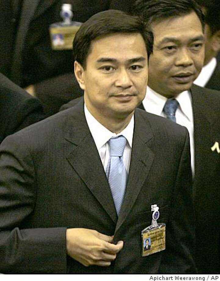 Leader of Democrat Party Abhisit Vejjajiva, center, leaves the parliament's chamber after being chosen to the country's new prime minister in Bangkok, Thailand, Monday, Dec. 15, 2008. Parliament chose the opposition party leader as Thailand's prime minister Monday following months of political chaos, as supporters of the former government tried to blockade lawmakers in the building. (AP Photo/Apichart Weerawong) Photo: Apichart Weerawong, AP
