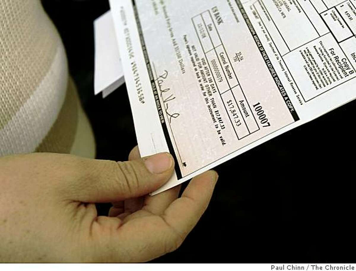 Francisca Amaral reviews a settlement check she received at her home in San Leandro, Calif., on Thursday, Dec. 18, 2008. Amaral was a lead plaintiff of a group of employees that successfully sued Cintas for back wages after the company was found to have violated a living wage law.