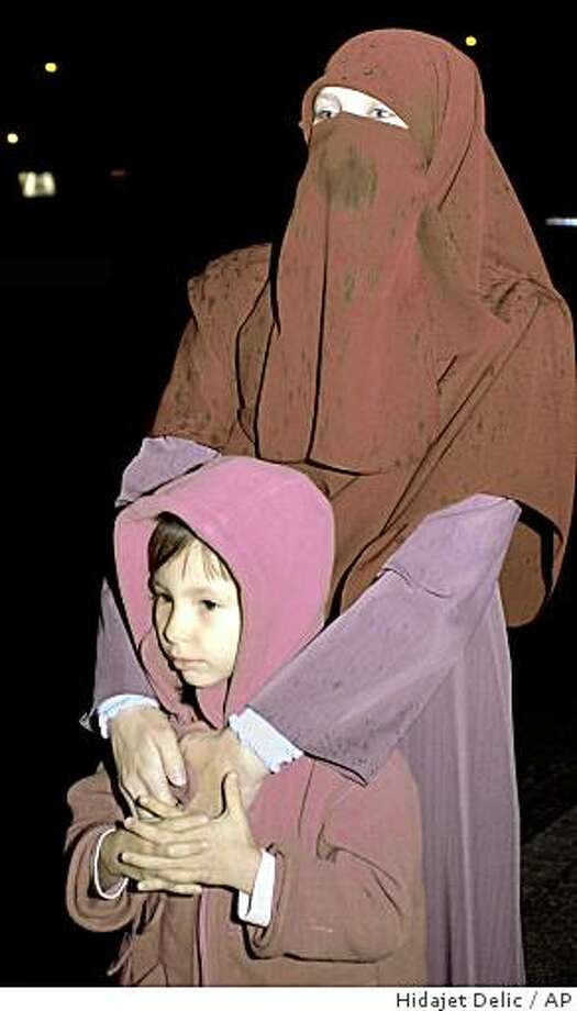 Nadja Dizdarevic, the wife of Gunatanamo prisoner Boudella al Hajj, holds her daughter Nur,  while waiting for his arrival at the airport in Sarajevo, Tuesday, Dec. 16, 2008. Hajj and two other Algerian-born naturalized Bosnians arrived home after having spent nearly seven years at the camp. Bosnia handed them over early 2002 to the U.S. under suspicion they were plotting to bomb the U.S. Embassy in Sarajevo. A judge in Washington ordered their release last month, saying the U.S. government's case was not strong enough to continue holding them. It was the first detainee transfer ordered by a U.S. federal judge.(AP Photo/Hidajet Delic) Photo: Hidajet Delic, AP