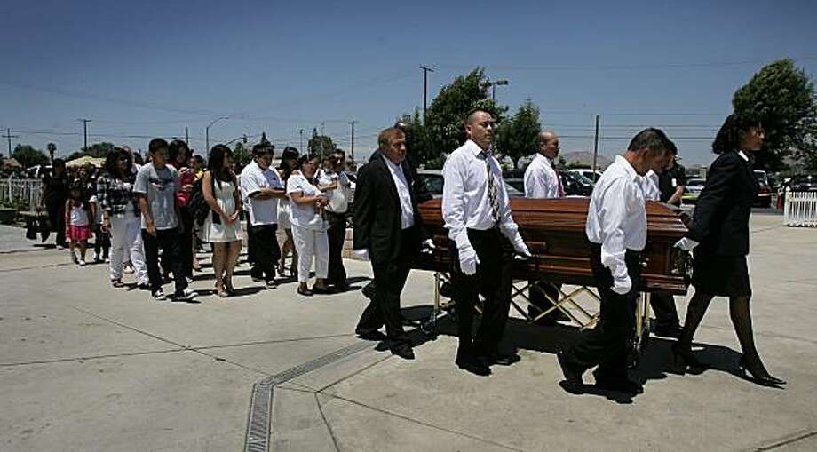 Family members follow the casket of murdered teen, Norma Lopez during the start of her funeral service on Thursday, July 29, 2010 at Saint Christopher's Catholic Church in Moreno Valley, Calif. (AP Photo/The Press-Enterprise, Stan Lim)  NO SALES; MAGS OUT; MANDATORY CREDIT Photo: Stan Lim, AP