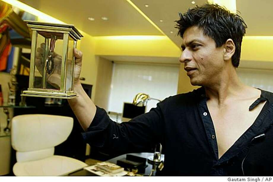 Bollywood actor Shah Rukh Khan looks at an award at his residence in Mumbai, India, Monday, Dec. 8, 2008. Khan, one of the biggest stars in the world's biggest movie industry, wept at a recent movie preview for Mumbai's shattered sense of security after militants laid waste to it in a bloody three-day attack. (AP Photo/Gautam Singh) Photo: Gautam Singh, AP
