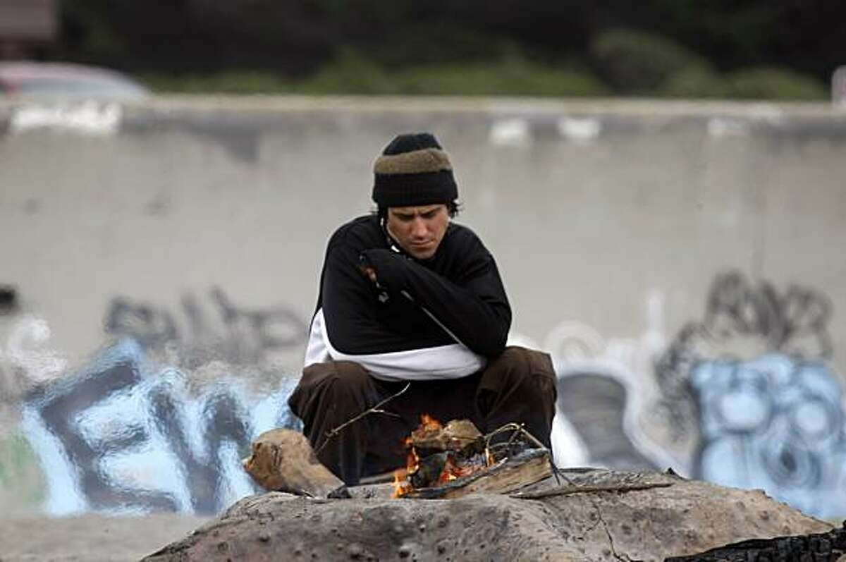 James Loehnis builds a fire on the beach to stay warm, Thursday July 29, 2010, at Ocean Beach in San Francisco, Calif.