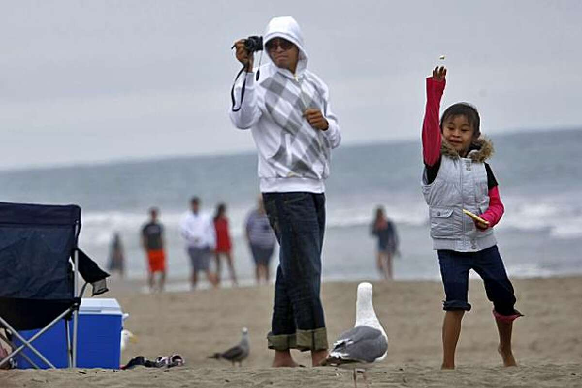Kit Campo takes a picture of his daughter Chloe as she plays with the seagulls at Ocean Beach, Thursday July 29, 2010, in San Francisco, Calif.