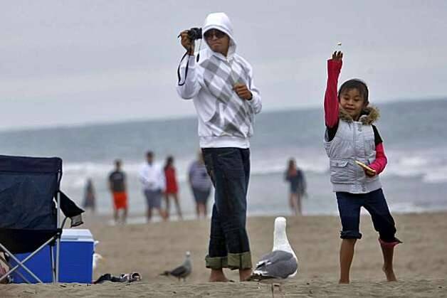 Kit Campo takes a picture of his daughter Chloe as she plays with the seagulls at Ocean Beach, Thursday July 29, 2010, in San Francisco, Calif. Photo: Lacy Atkins, The Chronicle