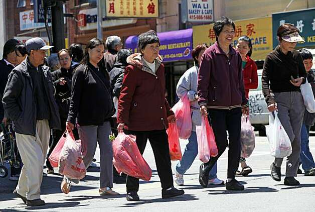 Shoppers in San Francisco China Town dressed for the cool weather as they cross Broadway.  San Francisco is experiencing the coldest summer in years. Visitors and residence alike have experienced the chill of fog for the past 25 of 28 days this month. Thursday July 29, 2010. Photo: Lance Iversen, The Chronicle