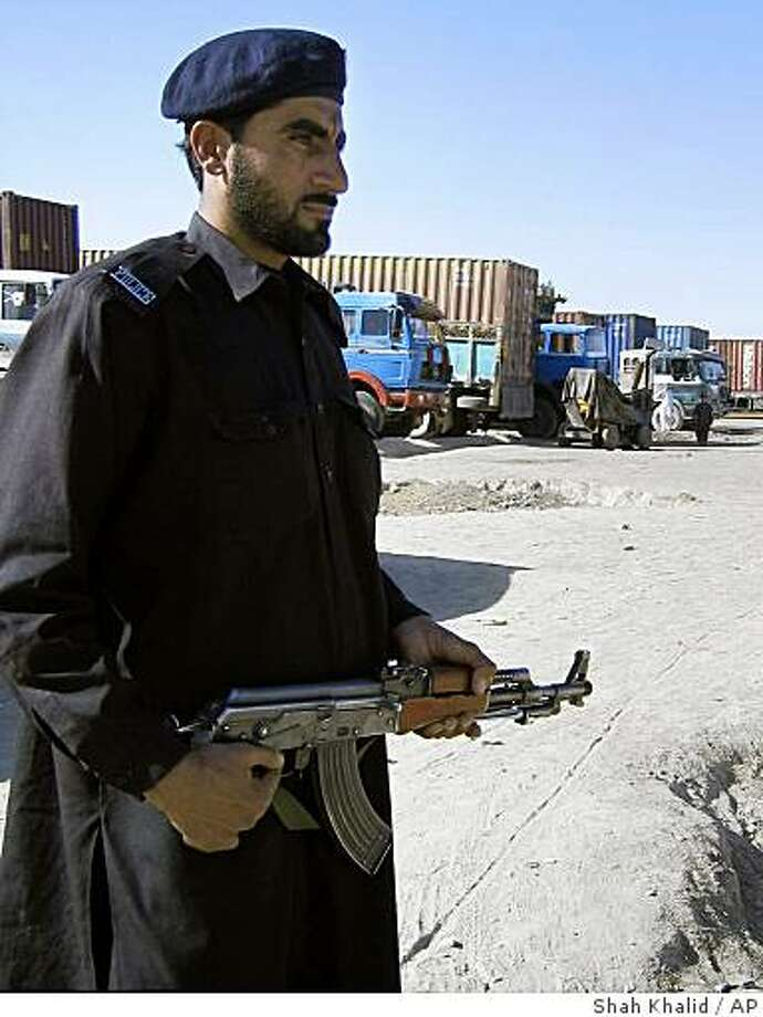 A Pakistani police officer stands guard next to vehicles loaded with supplies for U.S. and allied forces at the Pakistani border town of Chaman along Afghanistan on Sunday. Dec. 14, 2008. Attacks on terminals earlier in the week burned more than 200 vehicles and trailers, including about 70 Humvees, officials said. (AP Photo/Shah Khalid) Photo: Shah Khalid, AP