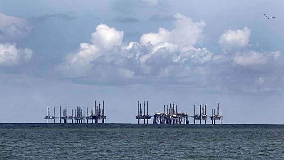 Semi-subermisible oil rigs and jackup shallow-water drilling units stand idle in the Gulf of Mexico off the coast of Cameron, Louisiana, U.S., on Saturday, July 17, 2010. The federal government has imposed a deepwater drilling moratorium and has slowed new shallow water permits in the wake of the BP Deepwater Horizon oil spill. BP Plc's oil spill may cost the U.S. Gulf Coast region 17,000 jobs and about $1.2 billion in lost economic growth by year-end even if the flow is stanched permanently next month, Moody's Analytics said. Photographer: Aaron M. Sprecher/Bloomberg Photo: Aaron M. Sprecher, Bloomberg