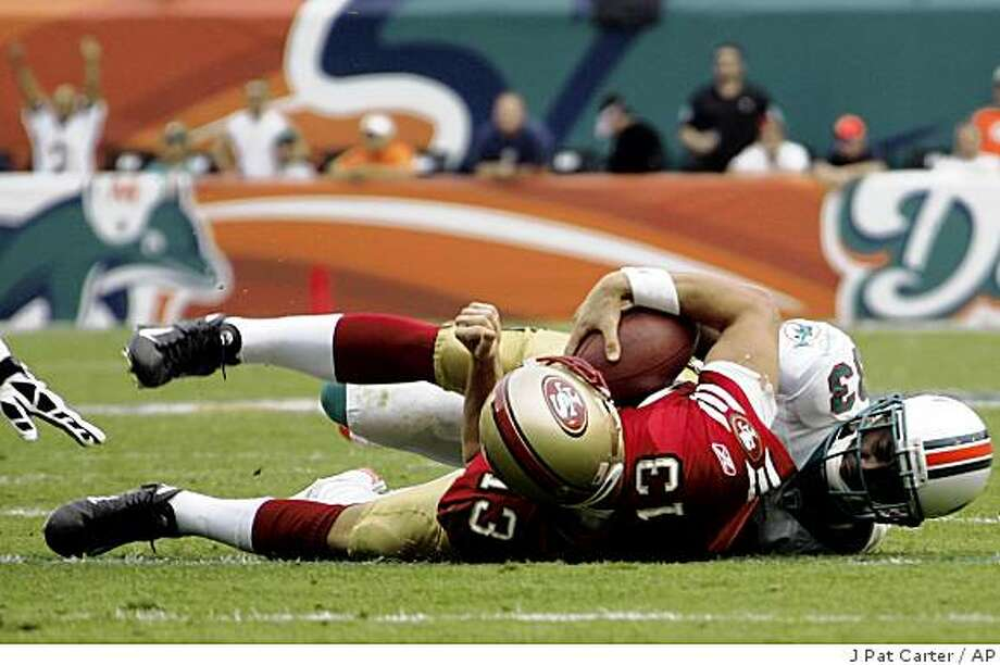 Miami Dolphins corner back Nathan Jones (33) tackles San Francisco quarterback Shaun Hill (13) during the fourth quarter of an NFL football game Sunday, Dec. 14, 2008 in Miami. The Dolphins won 14-9. (AP Photo/J. Pat Carter) Photo: J Pat Carter, AP