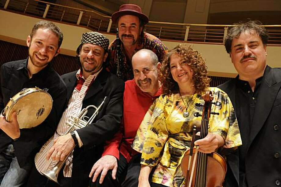 Members of the band The Klezmatics (from left to right: Richie Barshay (percussion), Frank London (trumpet, keyboards), Matt Darriau (kaval, clarinet, saxophone), Lorin Sklamberg (lead vocals, accordion, guitar, piano), Lisa Gutkin (violin, vocals), and Paul Morrissett (bass, tsimbl). Photo: Courtesy Of Lloyd Wolf