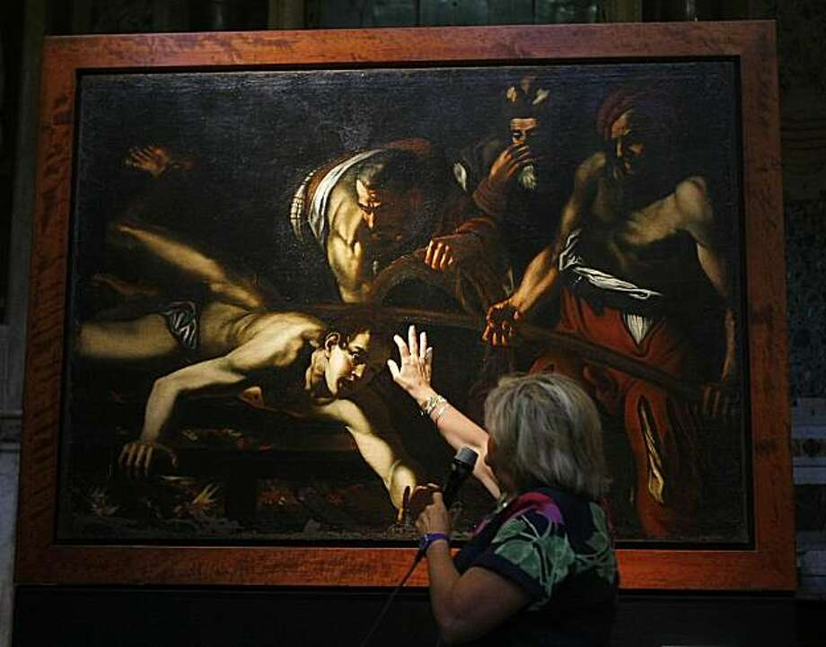"Art superintendent Rossella Vodret illustrates some detail of the painting at the center of the latest Caravaggio mystery, after the Vatican newspaper first suggested and then denied that the canvas was the work of the Italian master, in Rome, Italy, Tuesday, July 27, 2010. The ""Martyrdom of St. Lawrence"" would now be examined to ascertain its attribution, but Vodret and other Caravaggio scholars attending the unveiling agreed the painting did not look like a Caravaggio, but rather like the work of his followers. They said the quality did not hold up to Caravaggio's standards. Photo: Pier Paolo  Cito, AP"