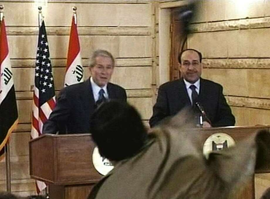 In this image from APTN video, a man throws a shoe at President George W. Bush during a news conference with Iraq Prime Minister Nouri al-Maliki on Sunday, Dec. 14, 2008, in Baghdad. The man threw two shoes at Bush, one after another. Bush ducked both throws, and neither man was hit. (AP Photo/APTN) Photo: AP