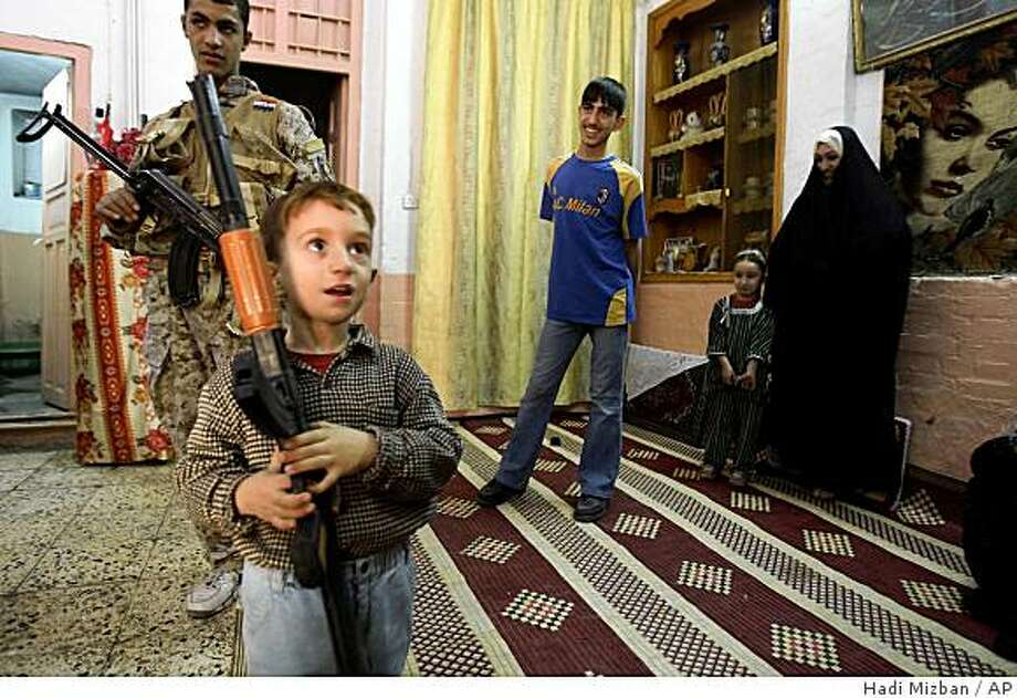 ** FILE ** In this Tuesday, Nov. 25, 2008 file photo, an Iraqi boy holds a toy gun, during a joint American and Iraqi military security sweep in the neighborhood of Sadriyah in Baghdad, Iraq.  With violence down and more children on the streets, U.S. soldiers in the city of Mahmoudiya, Iraq, south of Baghdad, have a new mission: clearing toy guns from the bustling shopping district. U.S. and Iraqi officers say the toys look so realistic that soldiers might mistake them for the real thing and open fire.  (AP Photo/Hadi Mizban, File) Photo: Hadi Mizban, AP