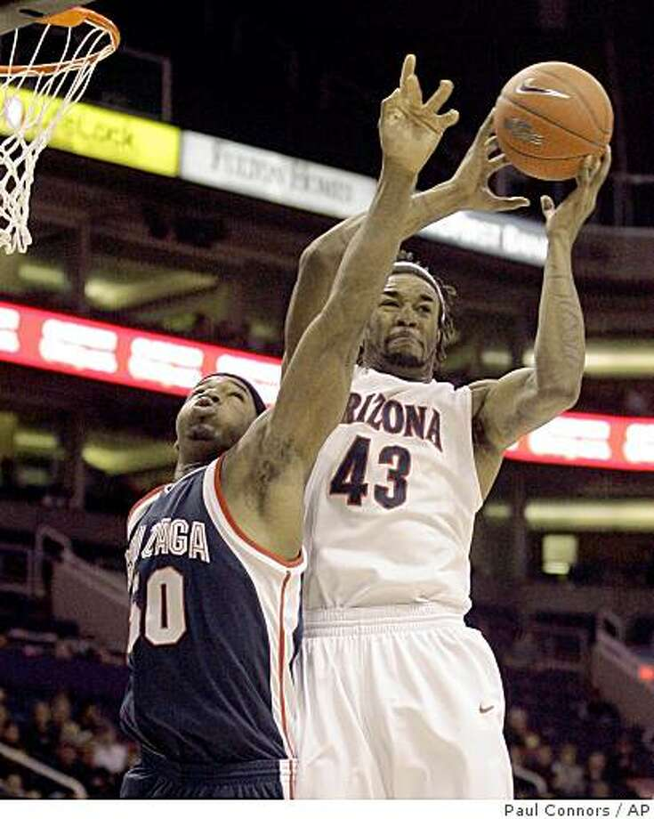 Arizona forward Jordan Hill, right, grabs a rebound over Gonzaga forward Ira Brown, left, in the first half of an NCAA college basketball game Sunday, Dec. 14, 2008, in Phoenix. (AP Photo/Paul Connors) Photo: Paul Connors, AP