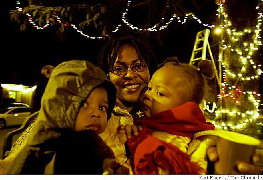 Towanda Gusters with her two kids Deontay one and Akeelah Two stayed warm as the Picardy drive lit their annual friendship Christmas tree and kicked off the holiday season with about twenty people on hand to watch. on Saturday Dec 13,  2008 in Oakland , Calif Photo: Kurt Rogers, The Chronicle