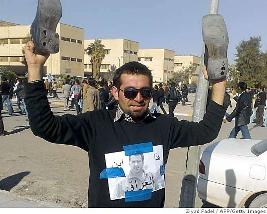 An Iraqi man holds up a pair of shoes with an image of arrested Iraqi journalist Muntazer al-Zaidi plastered to his jumper as he and others gather in the streets of the northern city of Mosul, 370km from Baghdad to protest his arrest, on December 16, 2008. Iraq faced mounting calls yesterday to release Zaidi who hurled his shoes at George W. Bush during a press conference in Baghdad two days ago, an action branded shameful by the government but hailed in the Arab world as an ideal parting gift to an unpopular US president.  AFP PHOTO / ZIYAD FADEL (Photo credit should read ZIYAD FADEL/AFP/Getty Images) Photo: Ziyad Fadel, AFP/Getty Images