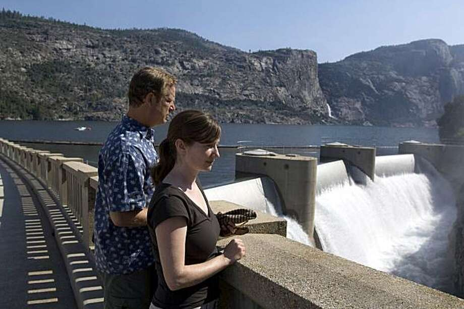 "Environmental Defense analyst Spreck Rosekrans, left, and fellow analyst Ann H. Hayden look over O'Shaughnessy Dam, Monday, July 24, 2006, near Yosemite National Park, Calif. With its soaring granite cliffs and spouting waterfalls, Yosemite's Hetch Hetchy Valley was described by conservationist John Muir as ""one of Nature's rarest and most precious mountain temples."" But much of the valley now lies submerged under 300 feet of water, after it was dammed and flooded more than 80 years ago to supply drinking water and hydropower to the San Francisco Bay area. (AP Photo/Al Golub) Photo: Al Golub, AP"