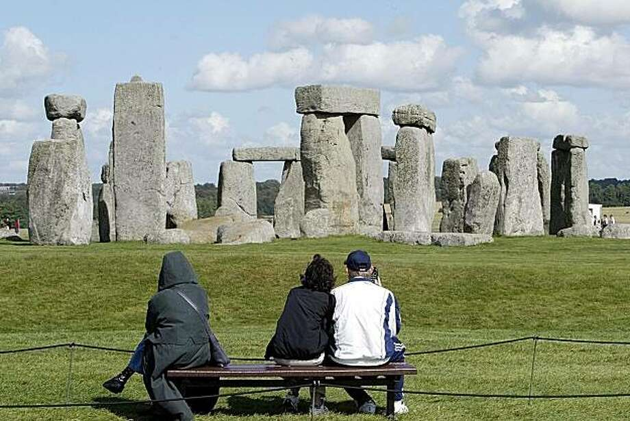 This is a Sept. 15, 2004. file photo of tourists looking at The Stonehenge on Salisbury Plain in England.  Scientists scouring the area around Stonehenge said Thursday July 22, 2010 they have uncovered the foundations of a second circular structure only a few hundred meters (yards) from the world famous monument. Photo: Dave Caulkin, File, AP