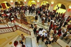Hundreds of employees of the University of California's Office of the President celebrate the holidays at their annual Christmas Party in the lobby of the Rotunda Building, Monday Dec. 15, 2008, in Oakland, Calif.