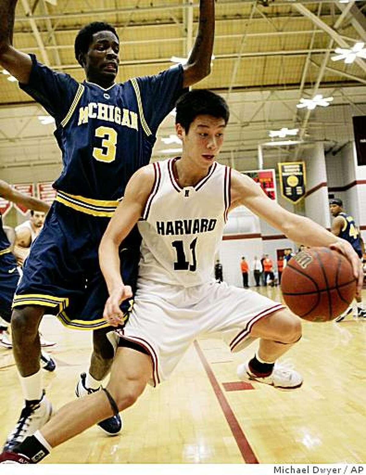 Harvard's Jeremy Lin (11) keeps the ball away from Michigan's Manny Harris (3) in the second half of a basketball game Saturday, Dec. 1, 2007, in Boston. Harvard won 62-51. (AP Photo/Michael Dwyer)