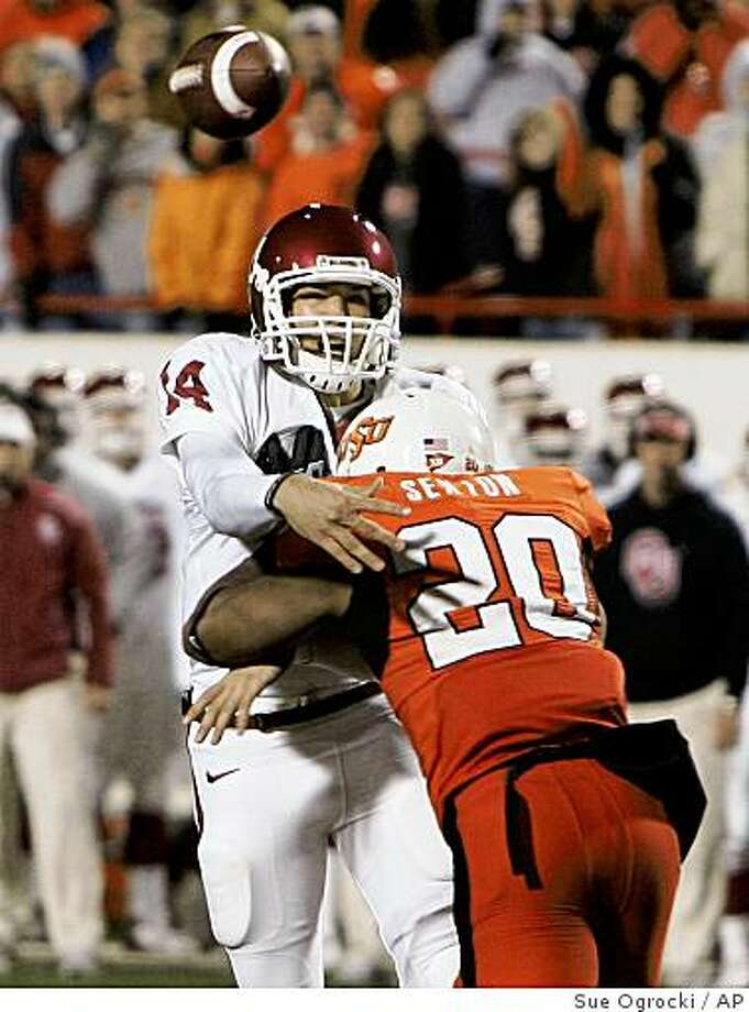 Oklahoma quarterback Sam Bradford (14) throws a touchdown pass to Oklahoma tight end Brody Eldridge under pressure from Oklahoma State defender Andre Sexton (20) in the fourth quarter of an NCAA college football game in Stillwater, Okla., Saturday, Nov. 29, 2008. Oklahoma won the game 61-41. (AP Photo/Sue Ogrocki) Photo: Sue Ogrocki, AP