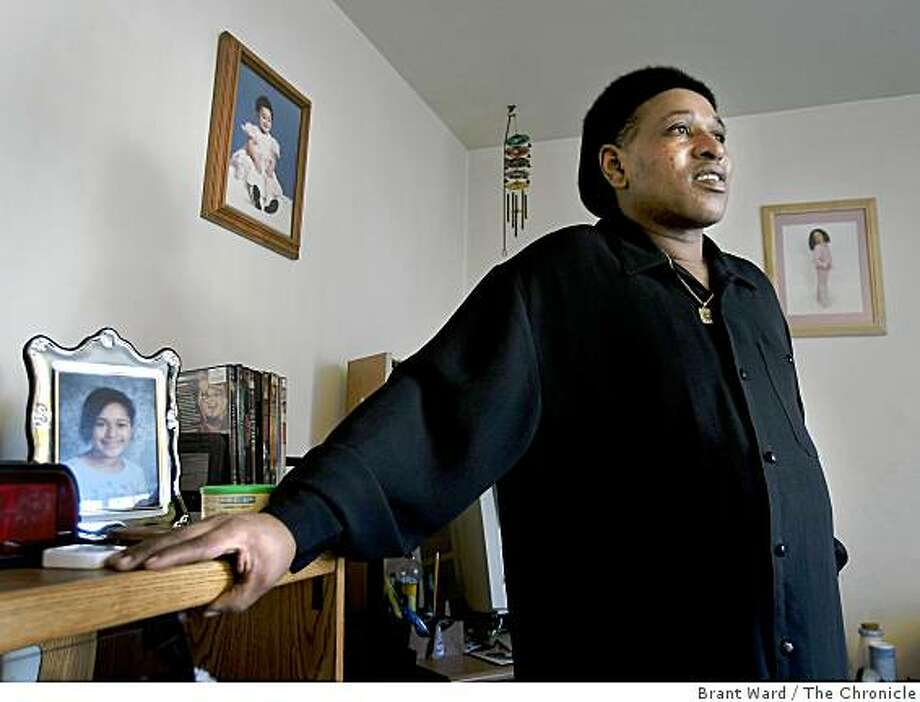 Gary Autrey stands in his small Oakland apartment surrounded by photographs of his daughter, who is an inspiration. Gary Autrey, an Oakland resident, whose bout with colon cancer is preventing him from working at his postal service job. Season of Sharing is helping him with rent and bill payments. Photo: Brant Ward, The Chronicle