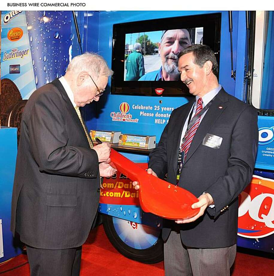International Dairy Queen, Inc. President and CEO John Gainor holds a 33-inch, red Dairy Queen(R) spoon for Warren Buffett to sign at the May 2010 Berkshire Hathaway shareholders meeting. The iconic red spoon is listed on eBay(R) to benefit Children's Miracle Network. (Photo: Business Wire) Photo: Business Wire