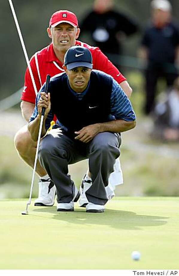 U.S. golfer Tiger Woods, right, and caddy Steve Williams check the line of a putt on the 9th green during the 3rd round of the American Express Golf Championship at The Grove, Chandler's Cross, England, Saturday Sept. 30, 2006. (AP Photo/Tom Hevezi)    Ran on: 10-22-2006Next!: The Oakland A's manager's job should be re-titled &quo;middle manager.&quo;Ran on: 10-22-2006Next!: The Oakland A's manager's job should be re-titled &quo;middle manager.&quo;Ran on: 10-22-2006 U.S. golfer Tiger Woods, right, and caddy Steve Williams check the line of a putt on the 9th green during the 3rd round of the American Express Golf Championship at The Grove, Chandler's Cross, England, Saturday Sept. 30, 2006. (AP Photo/Tom Hevezi) Photo: Tom Hevezi, AP