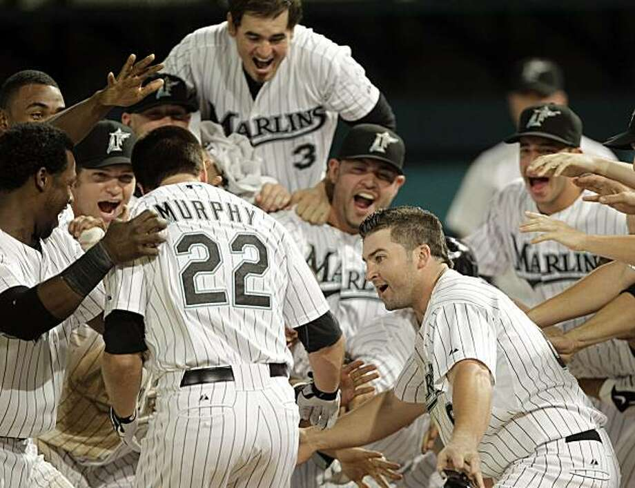 Florida Marlins' Donnie Murphy (22) is greeted at home plate after hitting a two-run home run against the Colorado Rockies in the ninth inning of a baseball game, Dan Uggla, right, scored on the home run, in Miami, Monday, July 19, 2010. The Marlins won 9-8. Photo: Alan Diaz, AP