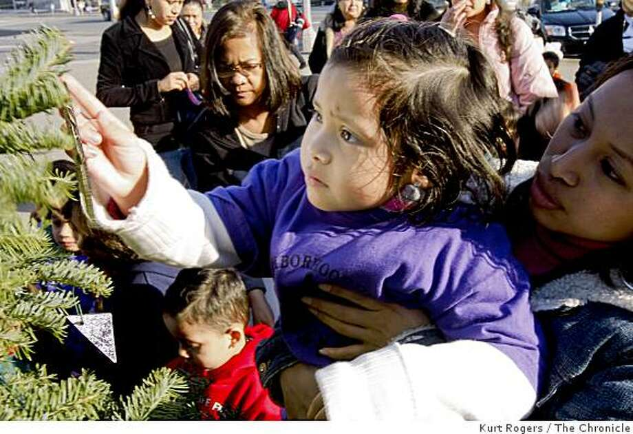 With help Daniela Chulim 4 hangs an ornament on the Christmas tree near the Children's playground in Civic Center on Friday Dec 12,  2008 in San Francisco, Calif Photo: Kurt Rogers, The Chronicle