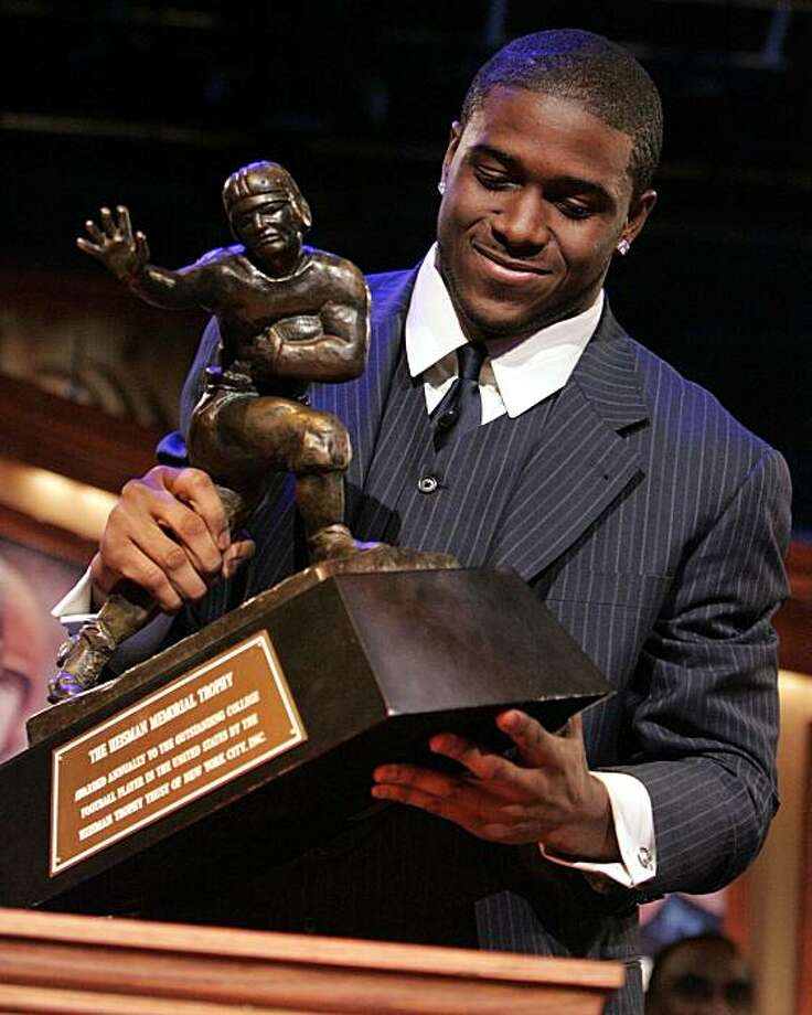 Southern California tailback Reggie Bush picks up the Heisman Trophy after being announced as the winner of the award Saturday, Dec. 10, 2005 in New York. Photo: Julie Jacobson, AP